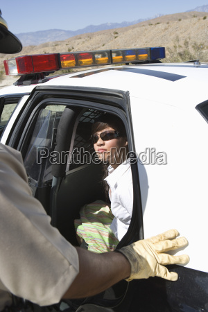 arrested woman sitting in police car