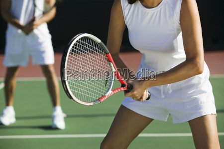 midsection of mixed doubles tennis players