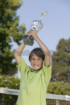 boy on tennis court holding up