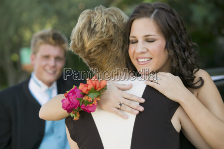well dressed teenagers hugging outside