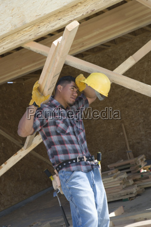 exhausted worker holding wooden beams