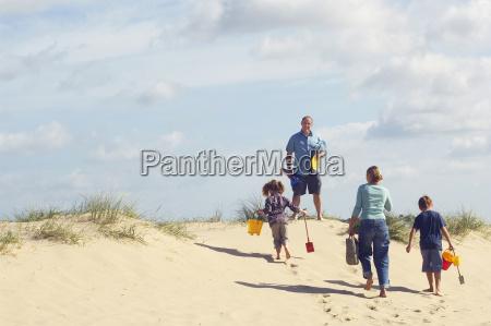 family walking up sand dune on