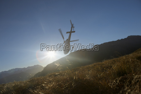 helicopter flying over hills in front