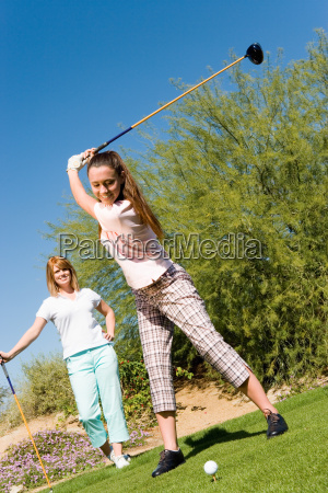 happy young woman playing golf