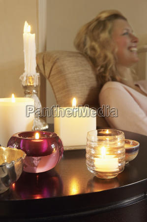 woman relaxing by table with lit