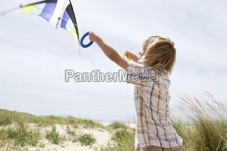 boy flying kite on a windy