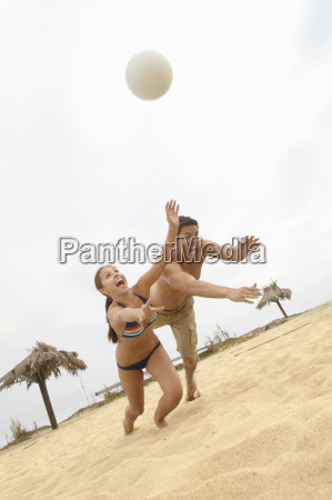 couple diving for volleyball on beach