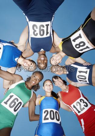 female athletes forming huddle against sky