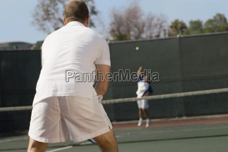 mid adult men playing tennis