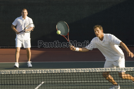 mid adult men playing tennis