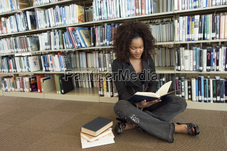 woman reading book while sitting on
