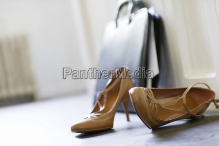 high heels and briefcase on floor