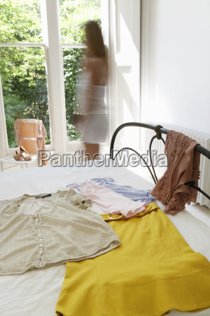 woman walking by outfit laid out