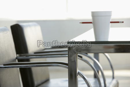 disposable cup pierced by pencil on