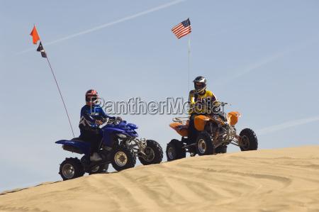 men with quad bikes on sand