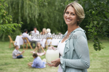woman holding pitcher of lemonade with