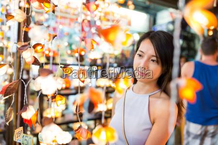 woman, choosing, lantern, in, street, market - 21416363