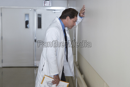depressed doctor leaning against wall