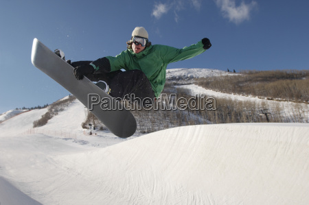 young snowboarder performing stunts on snowy