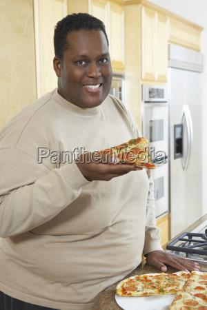 man holding slice of pizza