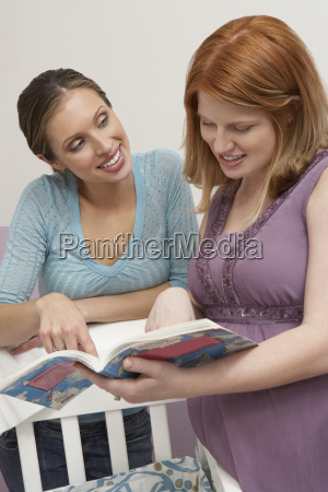 two women looking at book by