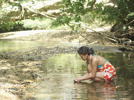 mixed race woman squatting in forest