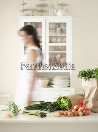 woman walking by fresh produce on