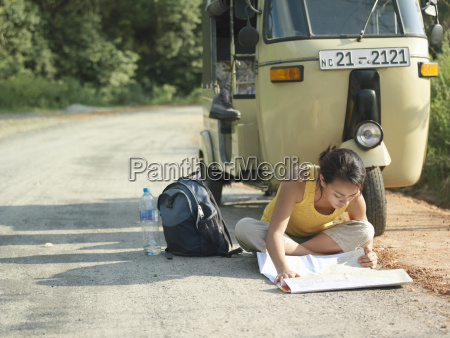 woman reading map on road by