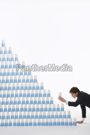 businessman stacking plastic cups into pyramid