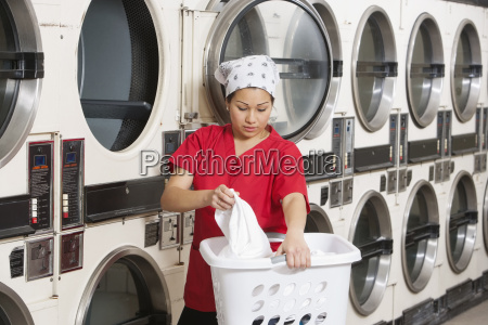 young female employee carrying laundry basket