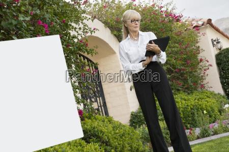 senior female agent reading from clipboard