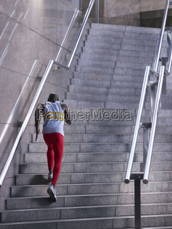 male athlete running up staircase outdoors