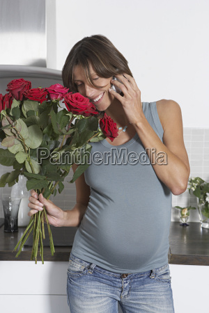 pregnant woman with cellphone and roses