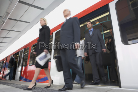 business commuters getting off train