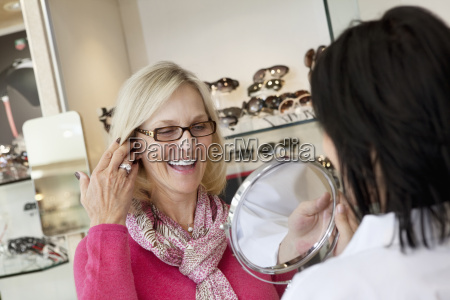 cheerful senior woman trying on glasses
