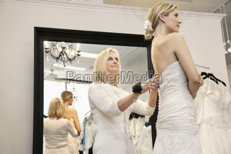 senior owner assisting young bride getting