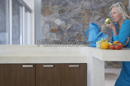 woman eating apple at kitchen counter