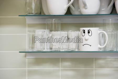 sad face mug on shelf