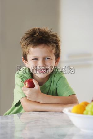 happy boy holding apple in kitchen