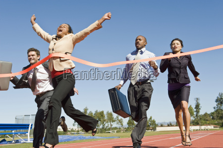 business people crossing the winning line