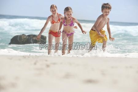 cheerful siblings running in water