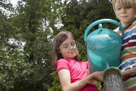 boy and girl watering garden