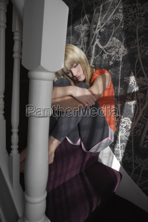 girl hugging knees on steps at
