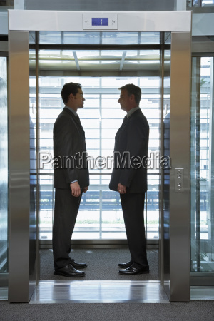 businessmen standing face to face in
