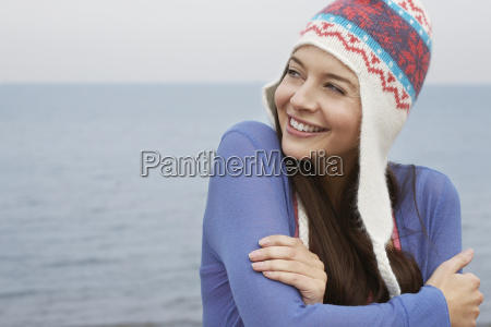 happy woman wearing knit hat standing