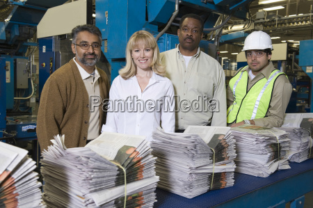 multiethnic operators with stack of newspapers