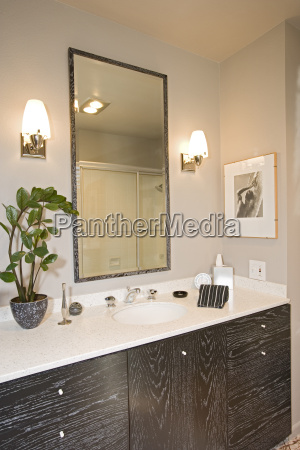 lamps by mirror over washbasin in