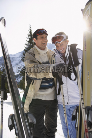 cheerful skiing couple in warm clothing