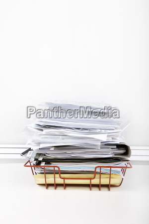 documents overflowing in desk tray against