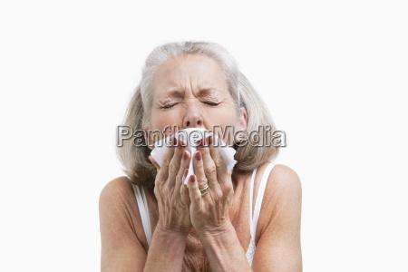senior woman sneezing into a tissue